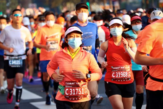 varios corredores corren el maratón de shanghái con una mascarilla puesta