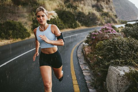 Female athlete running outdoors on highway