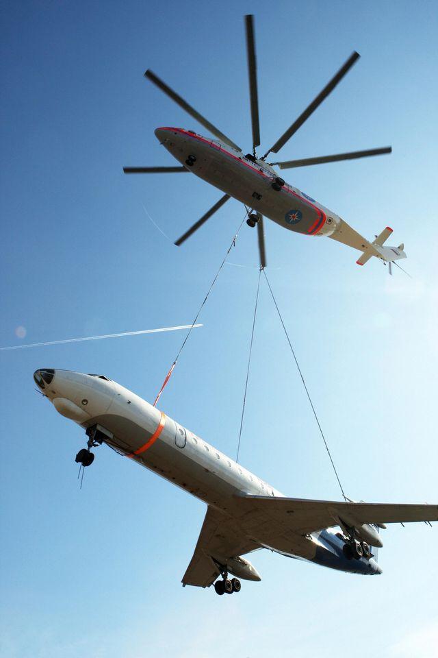 Um helicóptero Mi-26 levanta um avião Tu-134, 2009.