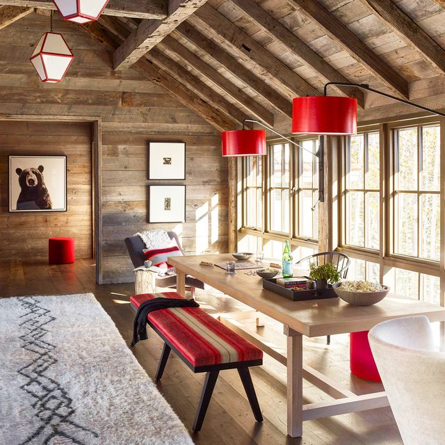 rustic decorating in room with wood paneled walls and red accents