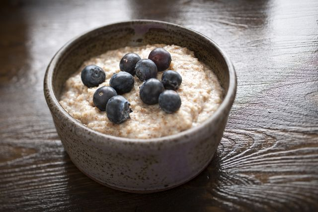 a rustiv bowl of porridge with blueberries