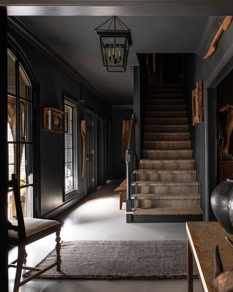 entryway, stairs, carpeted stairs, white tiles, black painted walls, black crown moulding