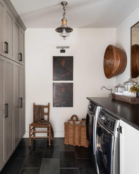 black tiling, wooden chair, washing machine and dryer, white painted walls, storage cupboards, dark quartz countertop