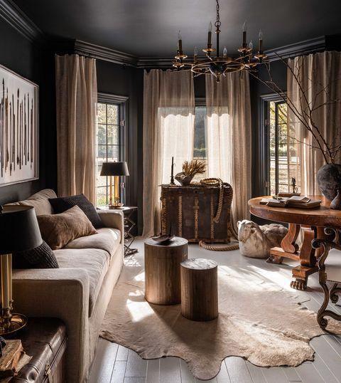living room, animal skin rug, wooden flooring, circular wooden coffee tables, black painted walls