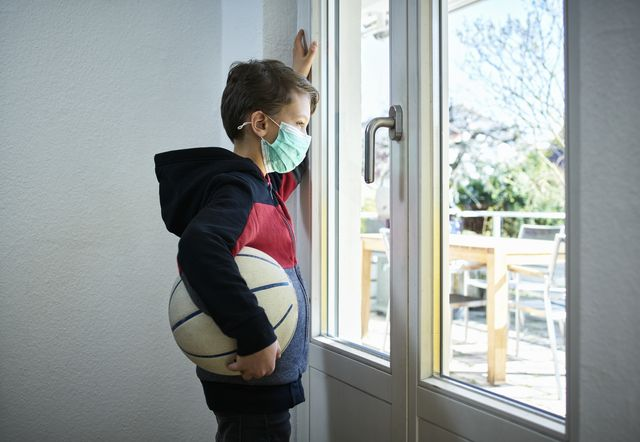 sad boy with basketball and mask looking out of window