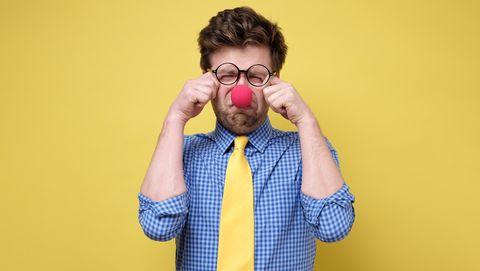 witte man met clownsneus en bril moet huilen