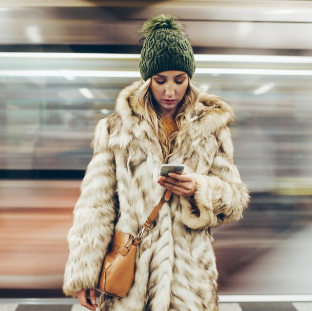 sad girl using her phone while standing on a subway platform