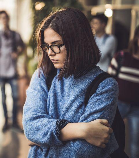 Sad high school student feeling lonely in a hallway.