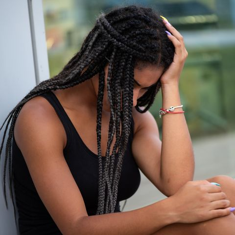 sad teen woman in deep sorrow sitting outside