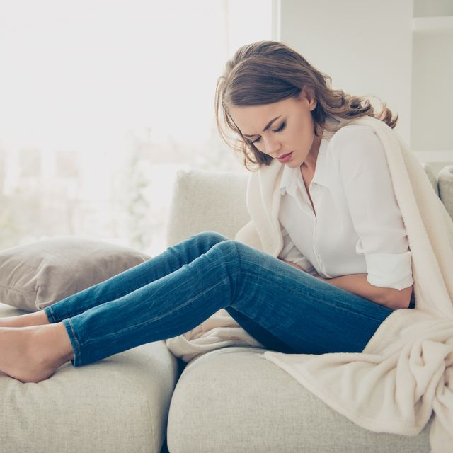 sad, upset, unhappy woman holding hands on stomach suffering from abdominal pain with close eyes, having menstrual period, food poisoning, gastritis, diarrhea, feeling unwell sitting in livingroom