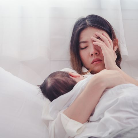 sad woman with baby lying on bed at home