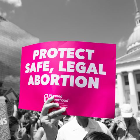 "woman holding sign that reads ""protect safe, legal abortion"""