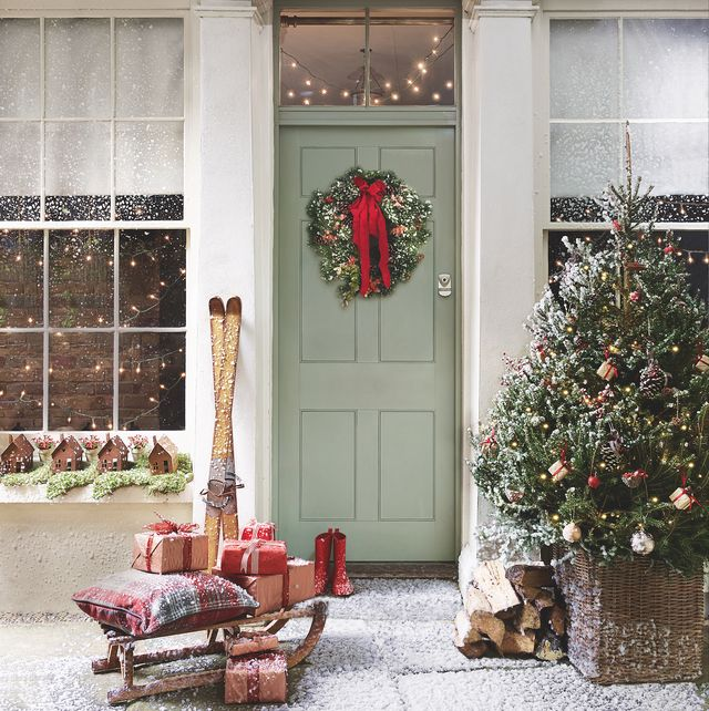 christmas green front door with christmas tree,sledge and gifts, wreath on door windows either sidesnow flakesrusty house tealight lanterns, £1550 each, cox  cox miniature potted berries, £6 each, john lewis vintage wooden skis, £85 vintage wooden sledge, £143 both nordic house copper wrapping paper, £1250 a 10m roll, cox  cox red poster paper, £450 a 10m roll ribbons, from a selection all hobbycraft check cushion, £16, next red wellingtons, £12 croft large rattan basket, £100 both john lewis fresh wreath made to order, from £25, kilburn flowers on tree miniature present decorations, £4 for six cinnamon stick decorations, £1 each small pine cone decorations, £ 3 for 12 all sainsbury's large pine cone decorations, £2 each large cinnamon stick decorations, £1 each red sparkly apple baubles, £2 for six champagne textured shatterproof baubles, £699 all tesco matt gold bauble, £6 for 12 metallic baubles from a selection all house of fraser