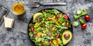 Salad with lamb's lettuce, tomatoes, avocado, parmesan and curcuma lemon dressing
