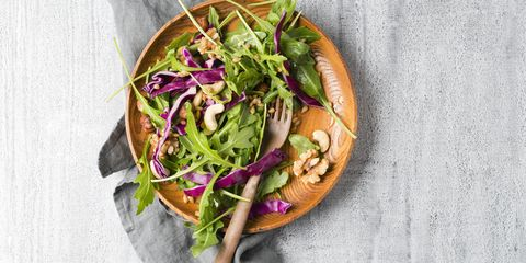 salad with red cabbage, rocket, einkorn wheat and various nuts on wooden plate