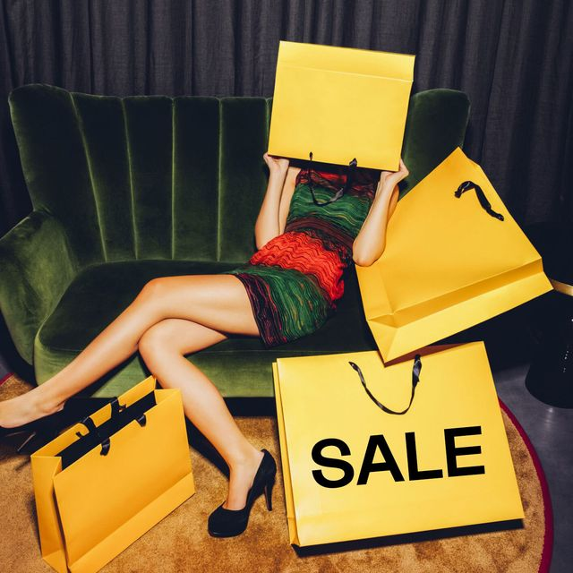 woman sitting with sale shopping bags