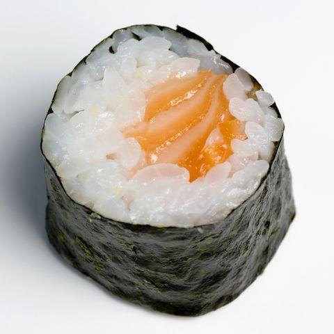 Wooden chopsticks next to salmon sushi piece