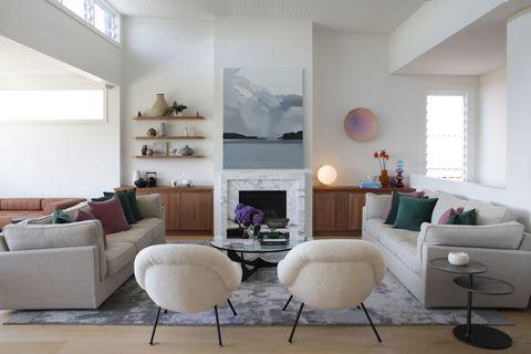 salón en tonos claros con chimenea de mármol en el centro en una casa de playa con materiales naturales en bondi beach,australia