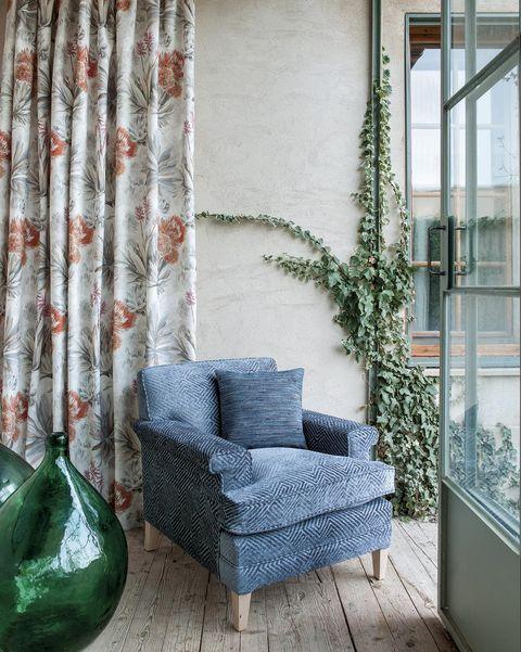 butaca azul en un salón con salida al jardín