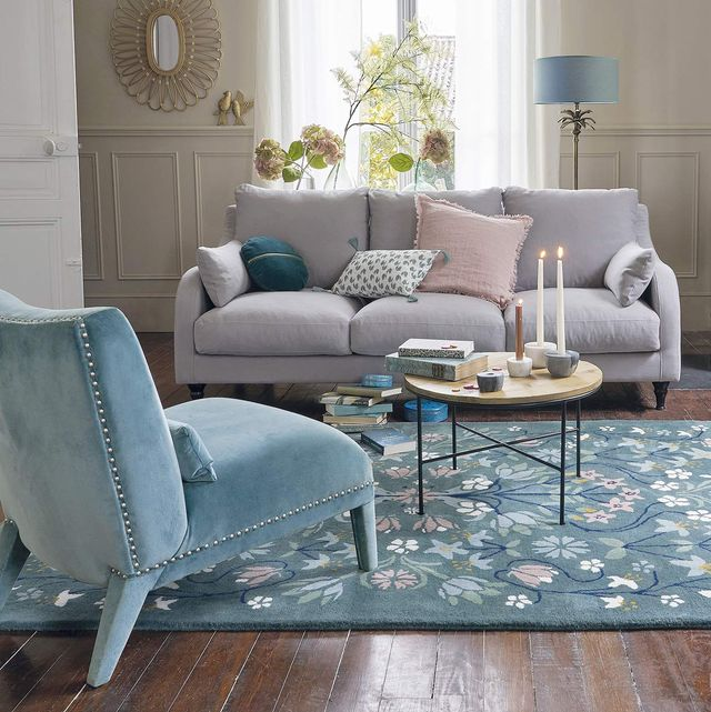 salón en tonos claros con lámpara de pie tras el sofá