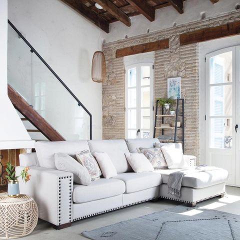 Salón blanco con pared de ladrillo y sofá con chaise-longue
