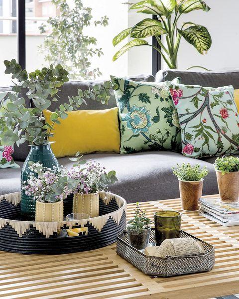 salón con sofá gris y cojines de colores con estampado de flores