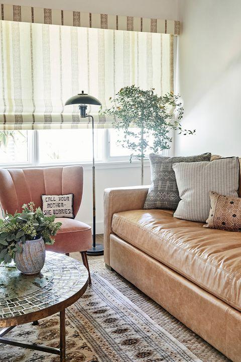 sofá de piel marrón y butaca art déco tapizada en terciopelo rosa