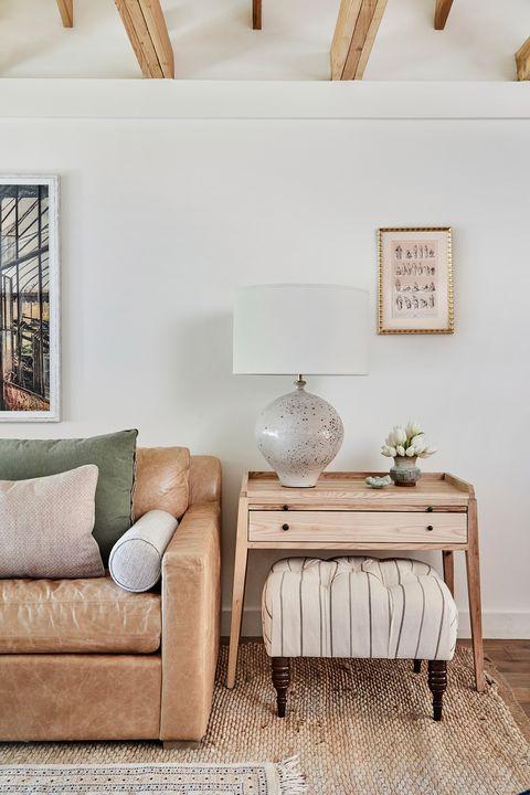 sofá de piel marrón envejecida y pequeño escritorio de madera con una otomana