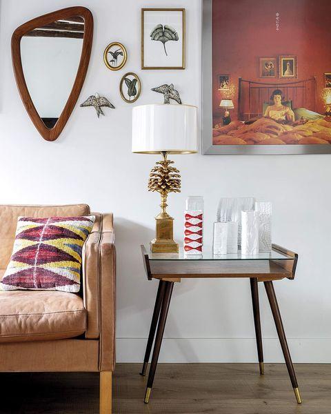 mesa auxiliar en el salón con lámpara de mesa con pie piña