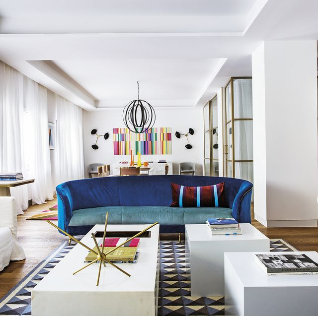 un trío irregular de mesas en laca blanca marca la disposición geométrica del salón la rectangular procede de rokc y los cubos son un diseño de lorena del pozo, autora de la decoración del espacio