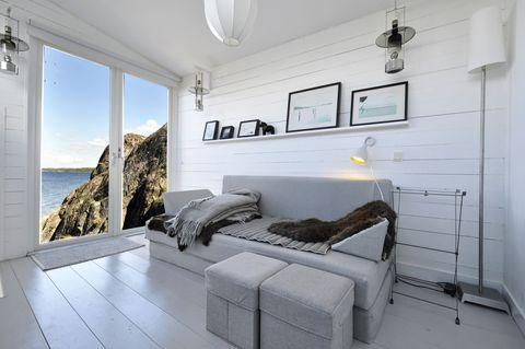 salón moderno con sofá y pufs grises con vistas al mar