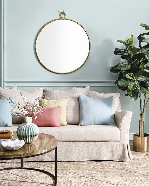 salones modernos paredes verdes con moldura y sofá beige
