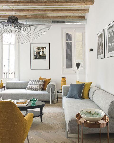 salón moderno con techo de vigas de madera y sofá gris