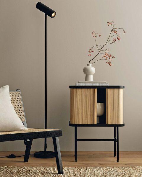 estilo japandi rincón con butaca de madera y rejilla con mesa auxiliar