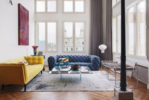 salón con sofás amarillo y azul en capitoné