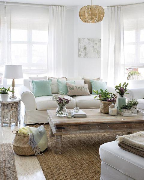Salón con sofá blanco y muebles de madera y fibra natural