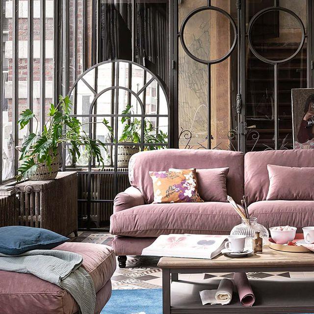 salón industrial con sofá rosa y espejo tipo ventana