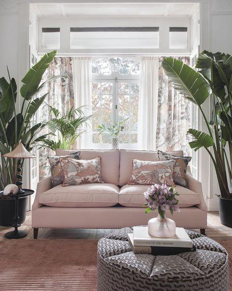 salón con sofá rosa y decorado con plantas