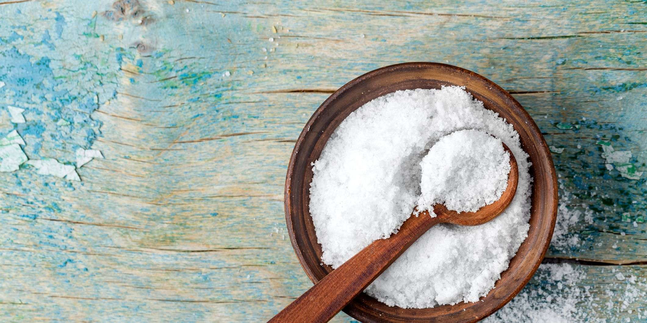 salt in wooden bowl with wooden spoon on blue wooden table, shot from above