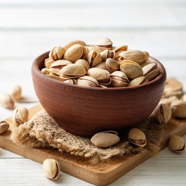 Salted pistachio nuts in ceramic bowl on white wooden background