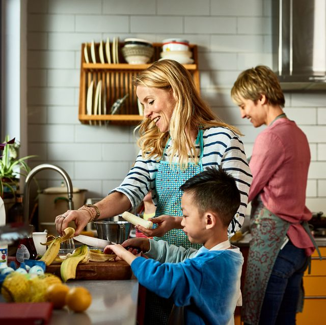 same sex couple cooking with son in kitchen