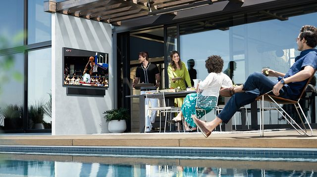 un grupo de amigos observa las imágenes que aparecen en un televisor samsung the terrace colgado en una pared en el exterior de una vivienda al lado de una piscina