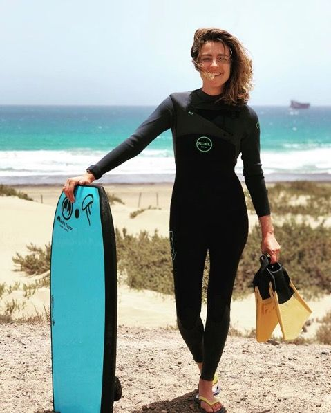 Wetsuit, Surfing Equipment, Personal protective equipment, Surfboard, Surfing, Bodyboarding, Standing, Surface water sports, Boardsport, Surfer hair,