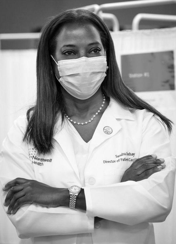 sandra lindsay wearing a white coat and blue surgical mask