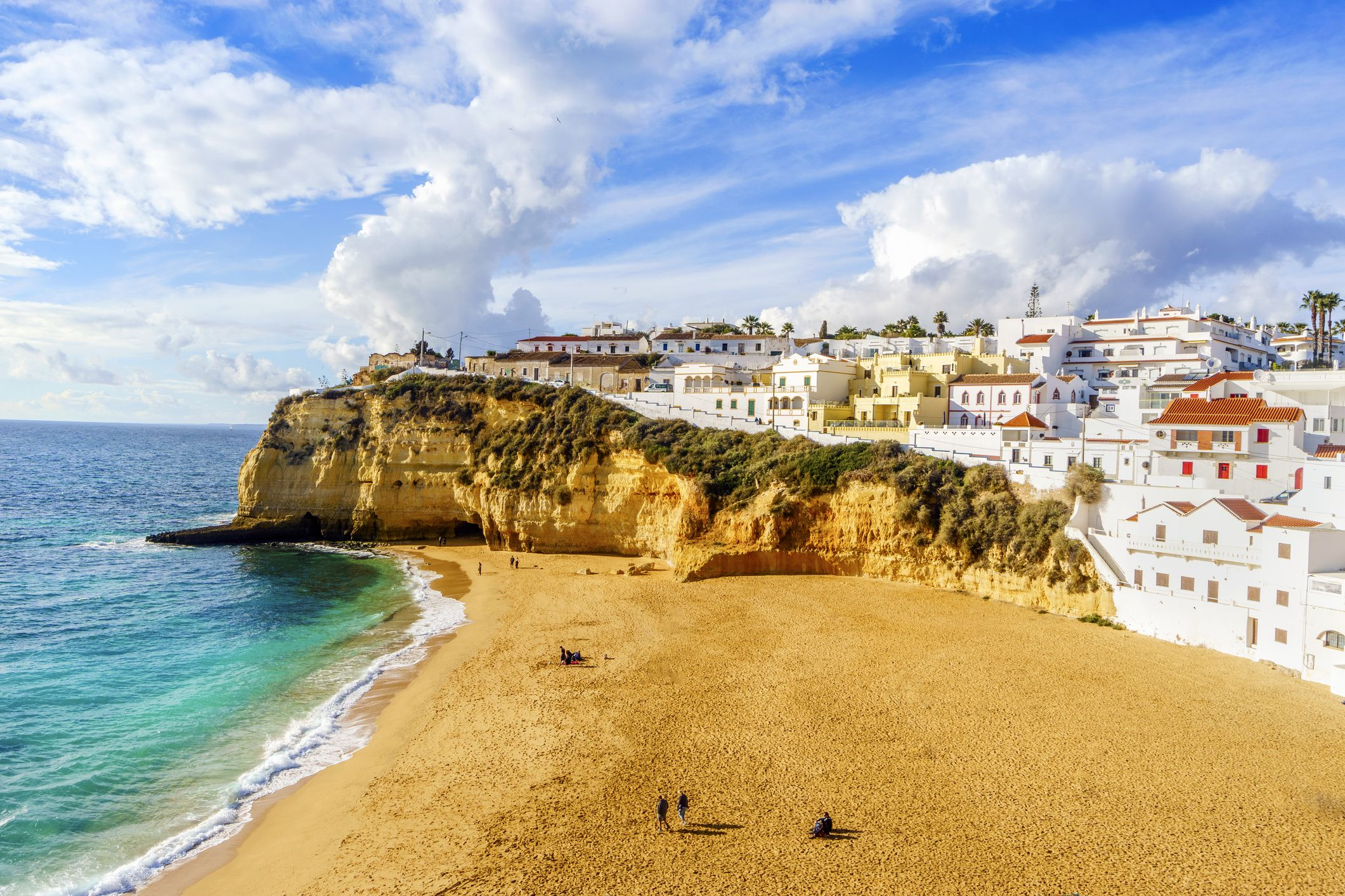 Sandy beach between cliffs and white architecture in Carvoeiro, Algarve, Portugal