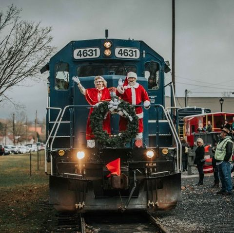 train pulling into the station, where people are waiting, with santa and mrs claus standing at the front of the train waving to everyone