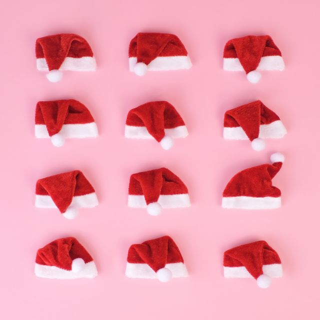miniature red santa hats arranged in a grid on a pink background