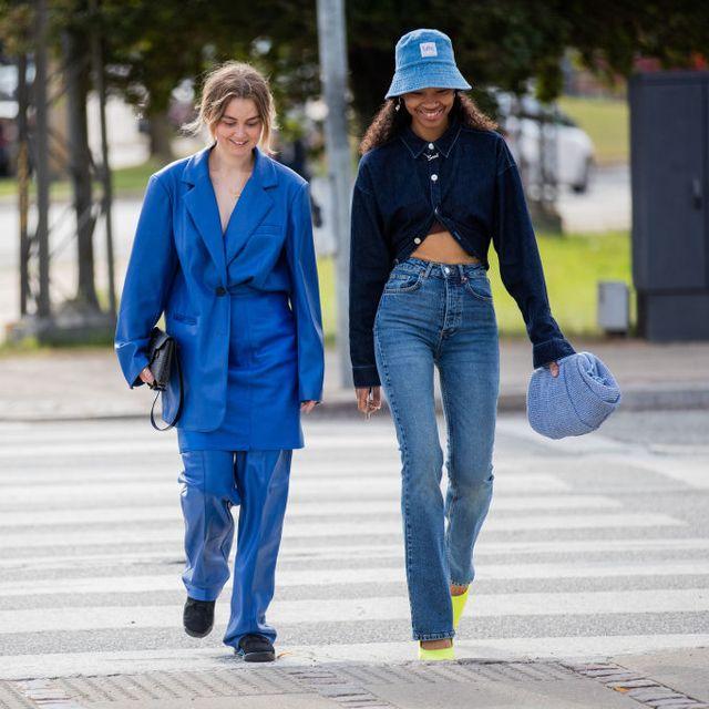 a woman walks at copenhagen fashion week wearing jeans