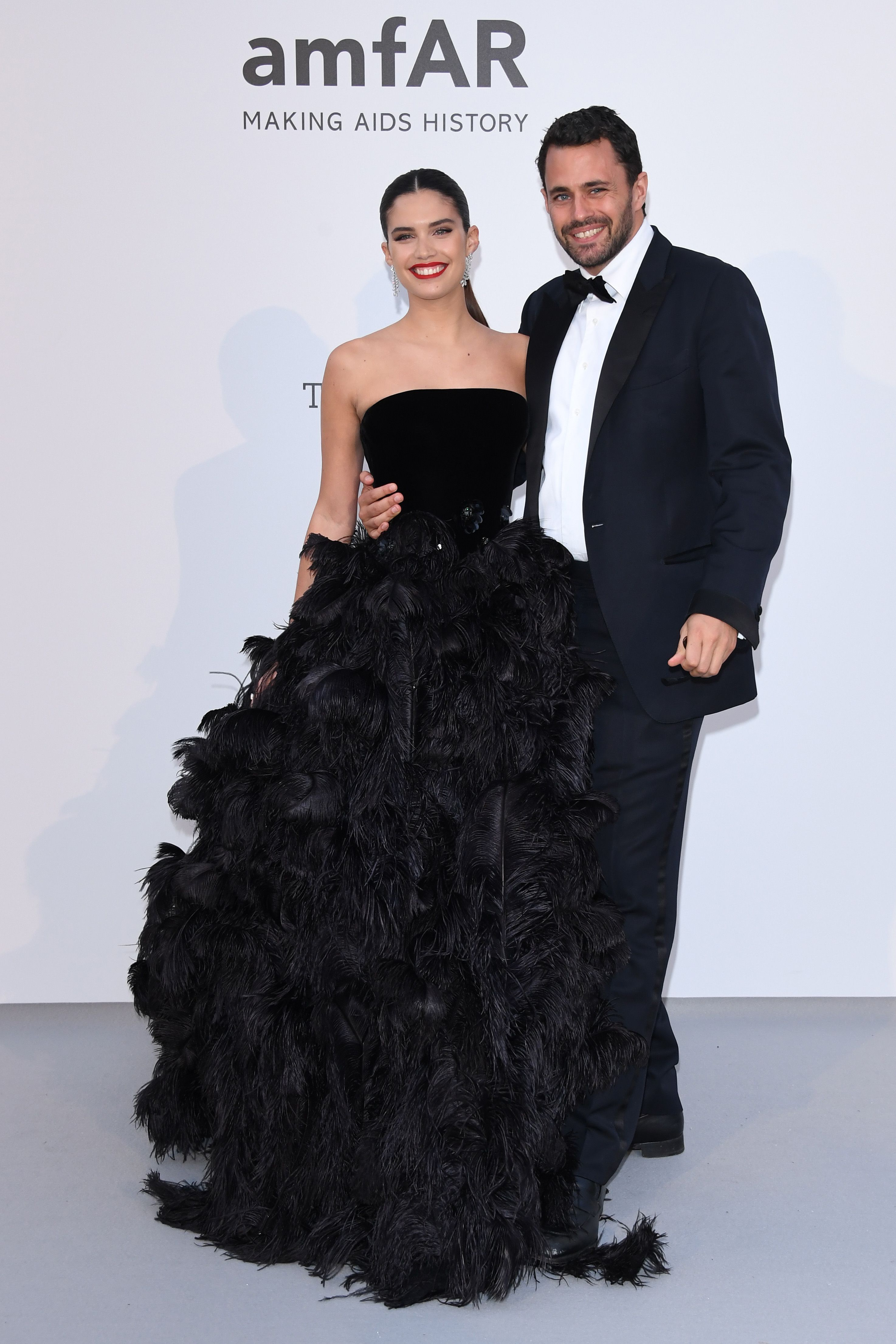 Sara Sampaio and Oliver Ripley Sampaio in a black strapless gown with a feathered skirt.