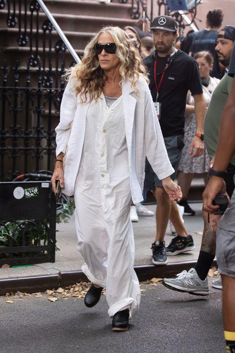 Η Σάρα Τζέσικα Πάρκερ με μακριά λευκή ολόσωμη φόρμα, σακάκι και τσόκαρα